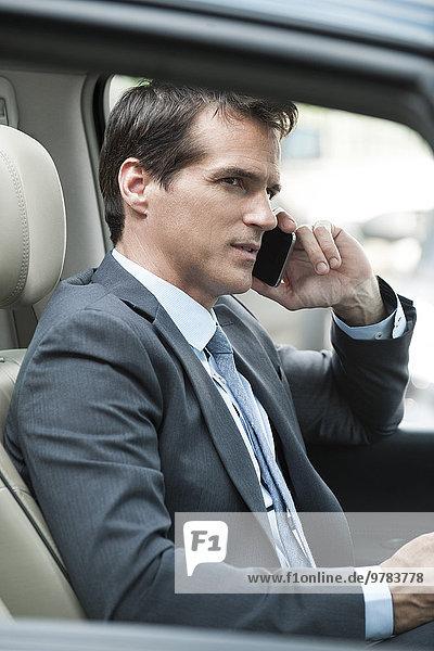 Mann spricht auf dem Handy während der Fahrt