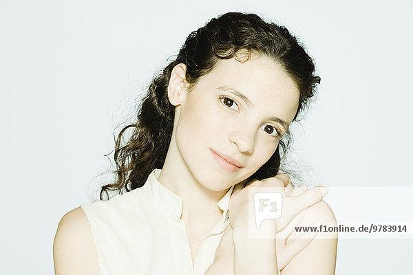 Junge Frau berührt die Schulter  lächelt in die Kamera  Porträt