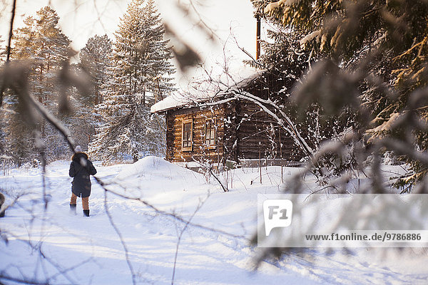 nahe Blockhaus Europäer Frau gehen Schnee Wald