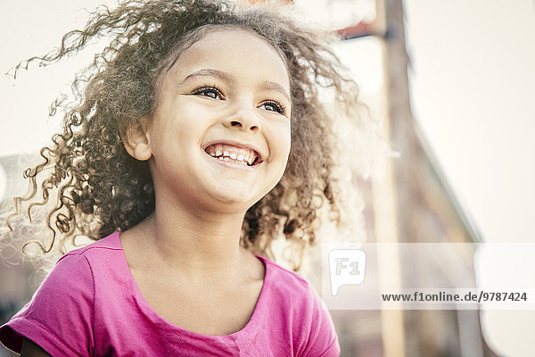 Low angle view of mixed race girl smiling outdoors