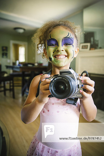 Mixed race girl in face paint photographing with camera