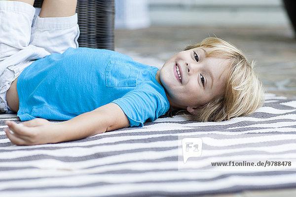 liegend liegen liegt liegendes liegender liegende daliegen Europäer lächeln Junge - Person Teppichboden Teppich Teppiche