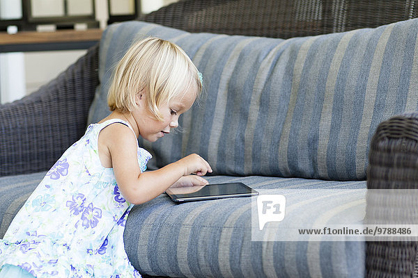 Caucasian girl using digital tablet on sofa