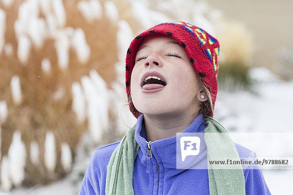 Caucasian girl catching snowflakes on tongue