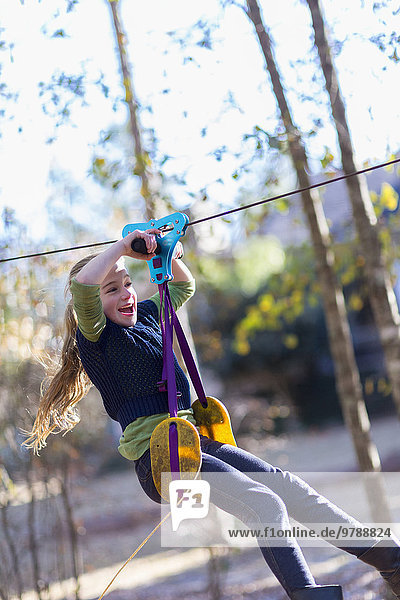 Caucasian girl zip lining in forest