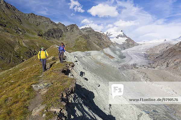 Ein Mann und eine Frau beim Wandern auf der Moräne des Findelgletschers an der Fluhalp  Zermatt  Wallis  Schweiz  Europa