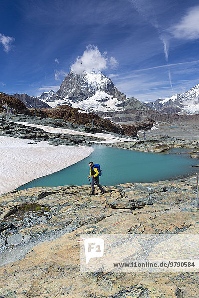 Hiker at glacier lake on the way to the Gandegg hut  the Matterhorn behind  Trockener Steg area  Zermatt  Canton of Valais  Switzerland  Europe