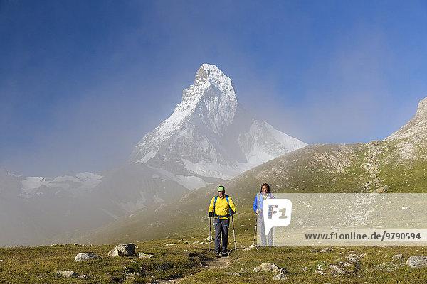Eine Frau und ein Mann beim Wandern am Wanderweg Höhbalmen  dahinter das Matterhorn  Zermatt  Wallis  Schweiz  Europa