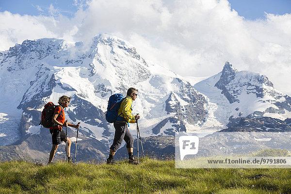 'Ein Mann und eine Frau beim Wandern  Plateau ''Schweifinen''  dahinter Breithorn und Klein Matterhorn  Zermatt  Wallis  Schweiz  Europa'