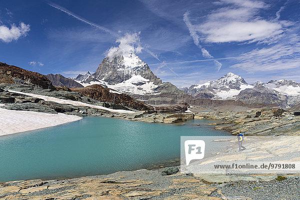 Wanderer an Gletschersee am Weg zur Gandegg Hütte  dahinter das Matterhorn  Gebiet Trockener Steg  Zermatt  Wallis  Schweiz  Europa