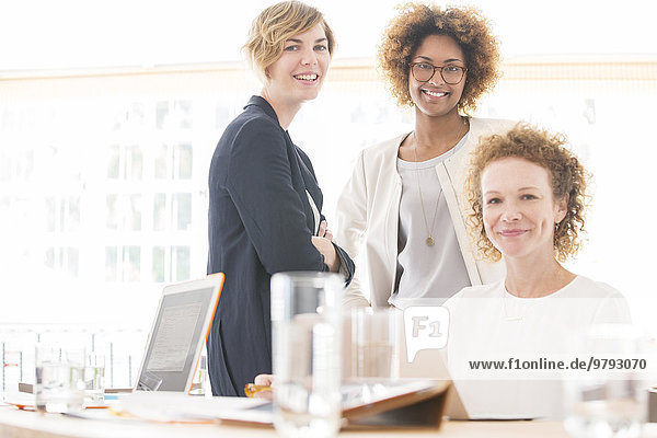 Porträt von lächelnden Büroangestellten am Schreibtisch