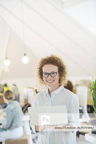 Porträt einer Frau mit Laptop im Büro