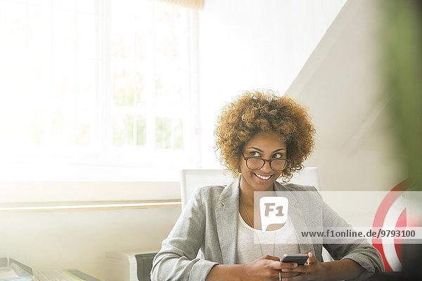 Porträt eines lächelnden Büroangestellten mit Smartphone