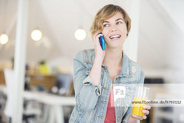 Büroangestellter spricht am Telefon und hält ein Glas Saft.