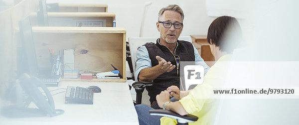 Zwei Büroangestellte im Gespräch am Schreibtisch