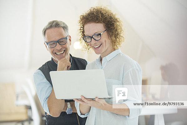 Zwei lächelnde Büroangestellte mit Laptop