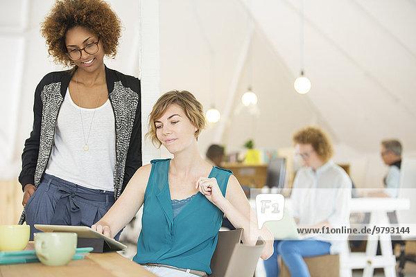 Zwei Büroangestellte sprechen am Schreibtisch mit dem Tablett