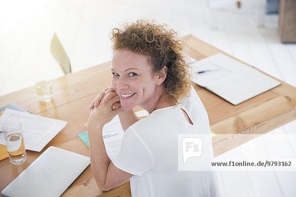 Porträt eines jungen lächelnden Büroangestellten am Schreibtisch