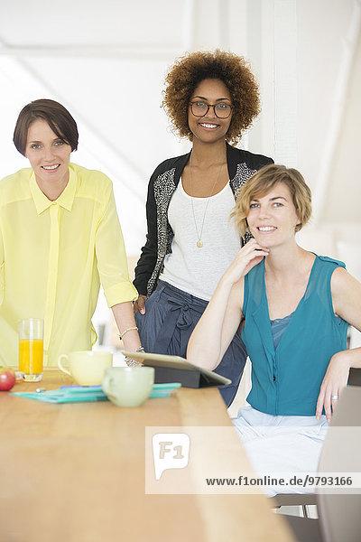 Lächelnde Büroangestellte sprechen in der Pause am Schreibtisch