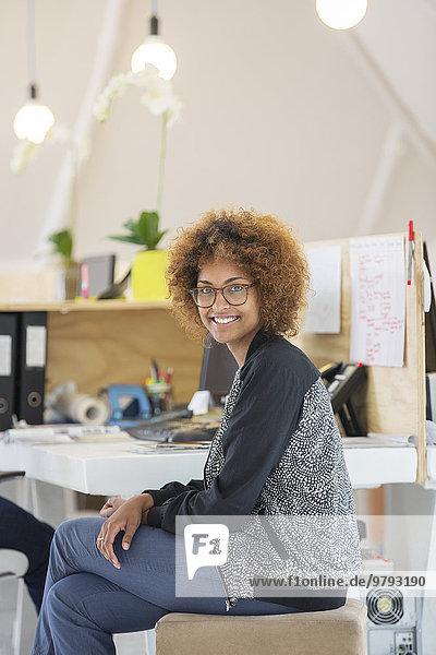 Porträt einer Frau im Büro sitzend und lächelnd