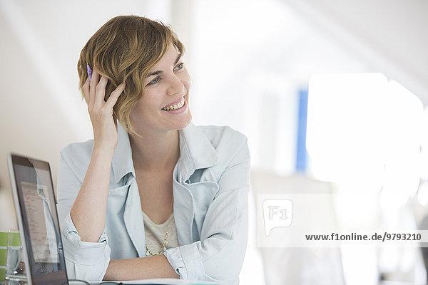 haltende Hand im Haar  Portrait der Frau mit lächelndem Laptop