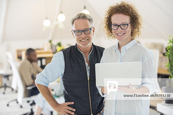 Portrait von Mann und Frau mit Laptop  lächelnd im Büro