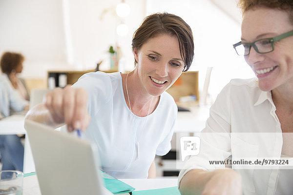 Frauen mit Laptop im Büro und lächeln