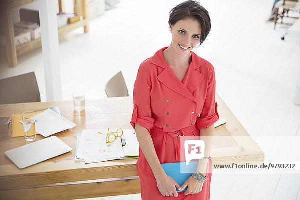 Porträt einer Geschäftsfrau in rotem Kleid  lächelnd im Büro