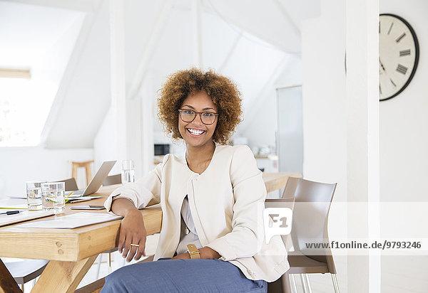Porträt einer Frau am Schreibtisch im Büro sitzend und lächelnd