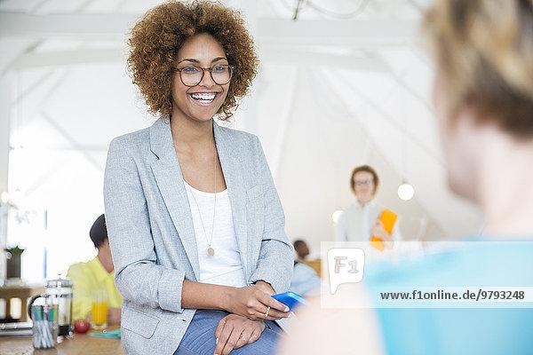 hält Smartphone und lächelt im Büro  Portrait der Frau mit Brille