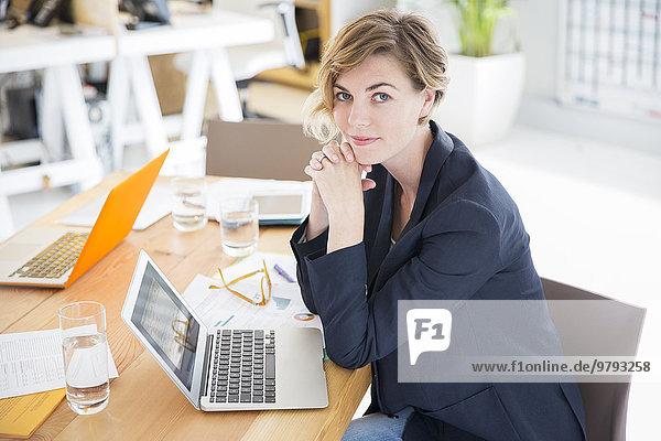 Porträt einer Frau am Schreibtisch mit Laptop im Büro