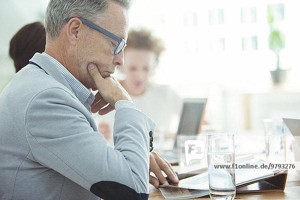 Porträt eines Geschäftsmannes  der im Konferenzraum sitzt und Zeitung liest.