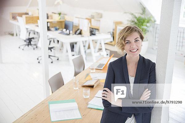 Porträt einer Frau  die sich im Büro an die Säule lehnt und lächelt