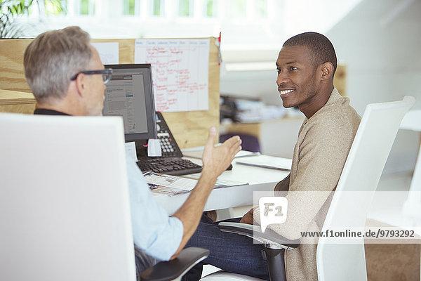Männer sitzen am Schreibtisch im Büro  reden und lächeln