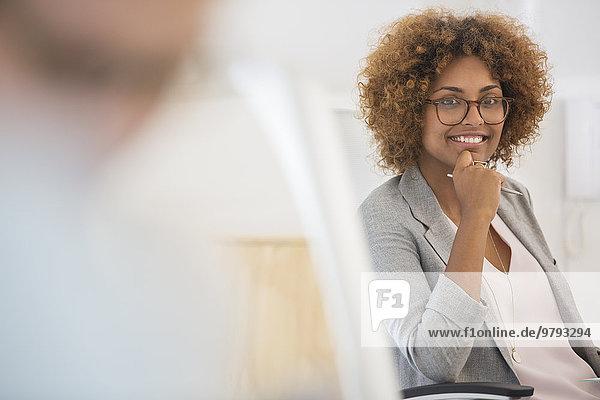Porträt einer Frau  die im Büro sitzt  eine Brille trägt und lächelt.