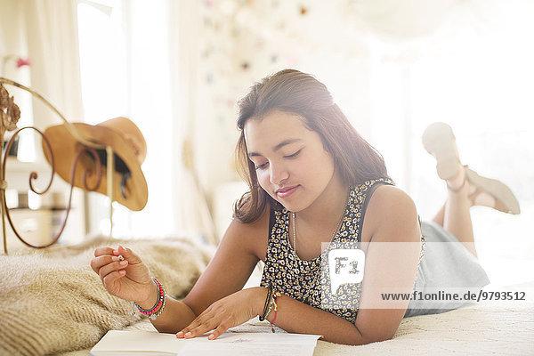 Teenagermädchen auf dem Bett liegend und im Notizbuch schreibend