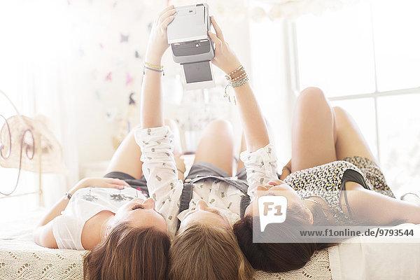 Drei Teenager-Mädchen nehmen Selfie  während sie im Schlafzimmer auf dem Bett liegen.
