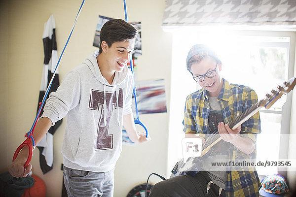 Zwei Teenager, die Spaß haben und E-Gitarre im Zimmer spielen.