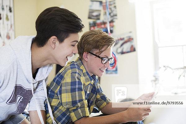 Zwei Teenager-Jungs haben Spaß bei der Benutzung des digitalen Tabletts im Zimmer