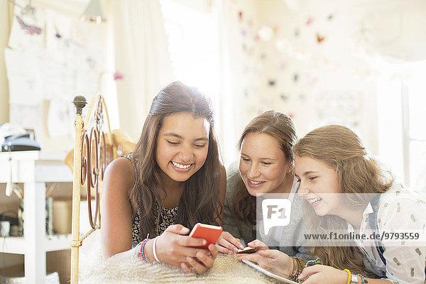 Drei Mädchen im Teenageralter, die zusammen auf dem Bett im Schlafzimmer liegen und ein Smartphone benutzen.
