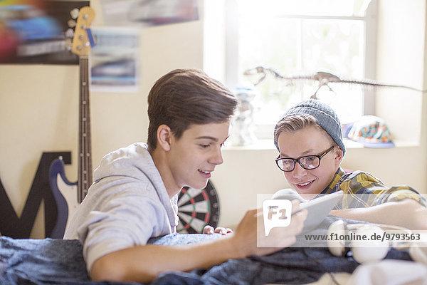 Zwei Teenager teilen sich ein digitales Tablett im Zimmer
