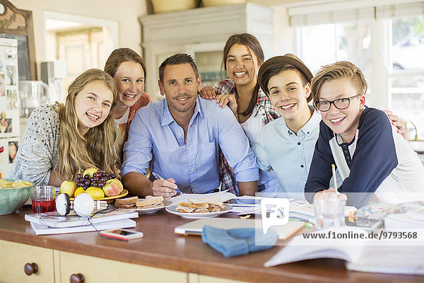 Gruppe von Teenagern mit einem erwachsenen Mann am Tisch im Esszimmer