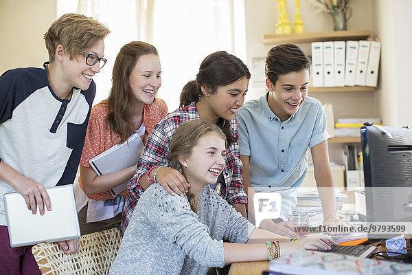 Gruppe von Teenagern, die gemeinsam den Computer im Zimmer benutzen