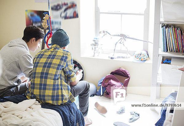 Zwei Teenager-Jungs sitzen auf dem Bett in einem unordentlichen Zimmer.