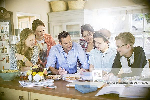 Gruppe von Teenagern mit einem Mann mittlerer Größe  der ein digitales Tablett am Tisch im Esszimmer benutzt.