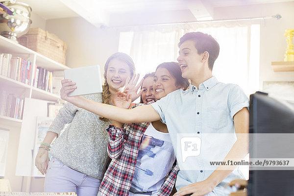 Teenager nehmen Selfie mit digitalem Tablett auf dem Zimmer