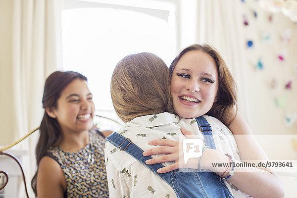 Drei Teenager-Mädchen umarmen sich im Schlafzimmer.