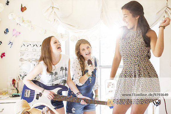 Drei Teenager-Mädchen beim Musizieren und Singen im Zimmer