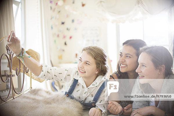 Drei Teenager-Mädchen  die Selfie im Bett im Schlafzimmer nehmen