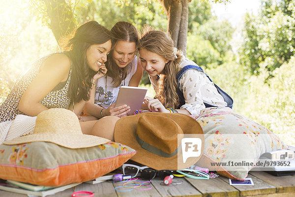 Drei Mädchen im Teenageralter mit digitalem Tablett im Baumhaus